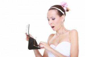 Braut schaut in leeren Geldbeutel ubnd staunt über die Preise von Hochzeitsfotografen
