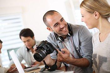 Fotograf zeigt Kundin Bilder auf seiner Kamera