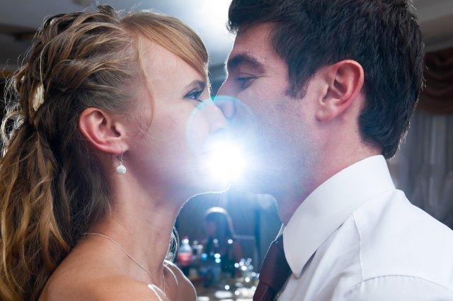 Brautpaar küsst sich auf Hochzeitsparty