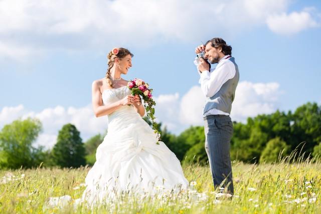 Hochzeitsfotograf fotografiert Braut auf Wiese