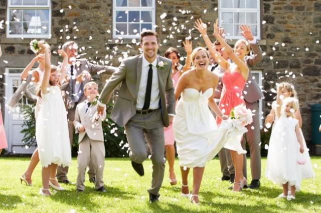 Brautpaar rennt durch fliegende Reiskörner