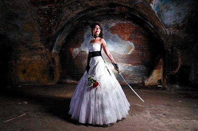 Braut mit schmutzigem Brautkleid und Schwert in der Hand