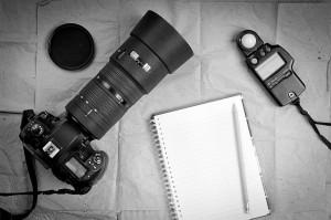 Kamera liegt mit Notizblock auf Tisch