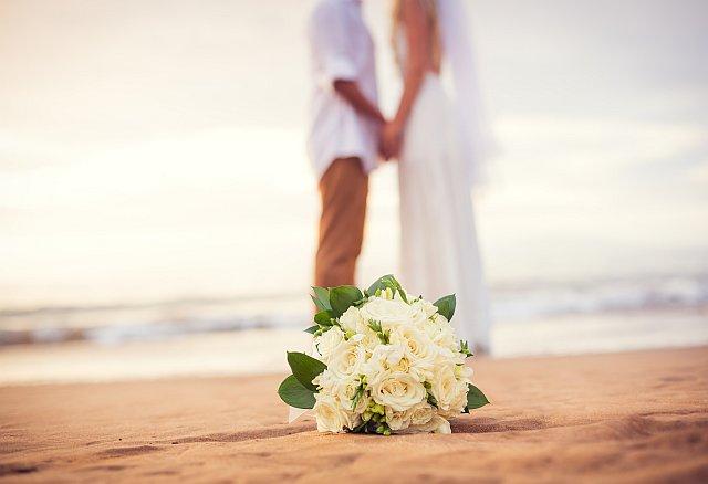 Brautpaar mit Brautstrauss im Ausland am Strand