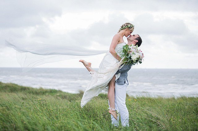 Brautpaar küsst sich am Strand