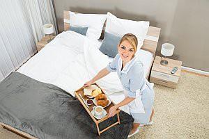 Zimmermädchen stellt Frühstück aus Bett im Hotelzimmer