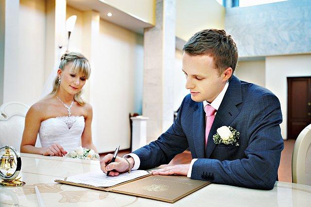 Bräutigam unterschreibt Urkunde im Standesamt