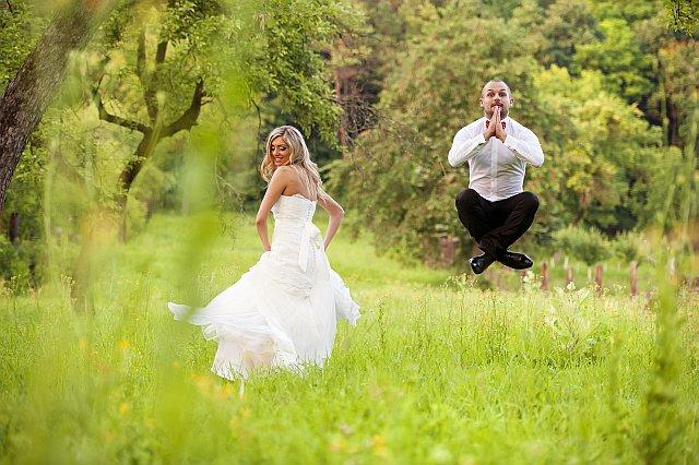 Bräutigam springt im Feld und kreuzt Beine in der Luft