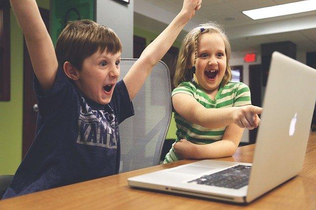Kinder spielen am Macbook