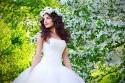 Junge Braut mit blühendem Apfelbaum im Hintergrund