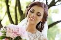 Schöne Braut strahlt über ihren Brautstrauß
