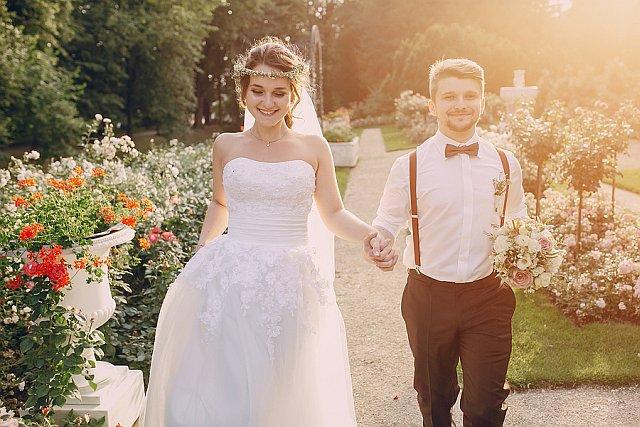 Brautpaar hält Händchen im Sonnenschein