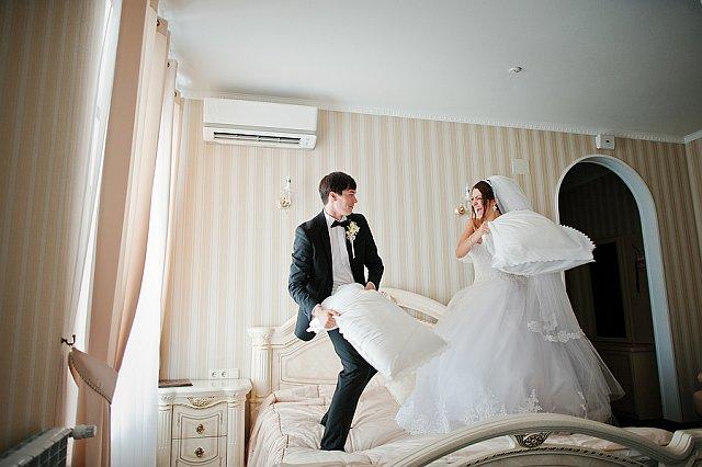 Brautpaar macht Kissenschlacht im Hotelzimmer