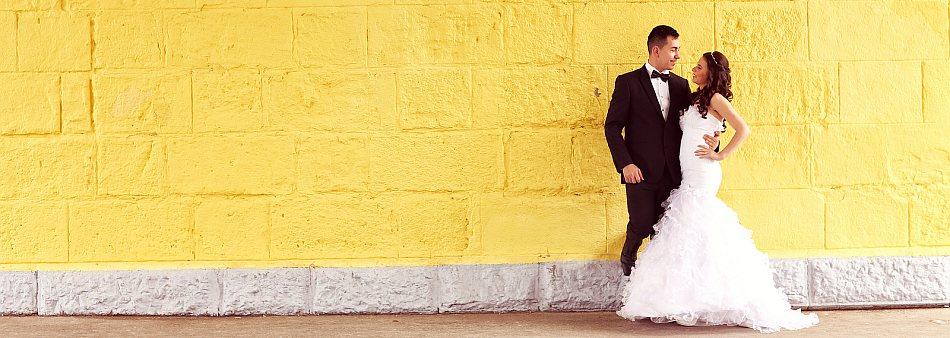 Brautpaar vor einer gelben Mauer