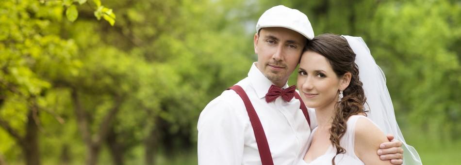 Brautpaar umarmt sich auf grüner Wiese