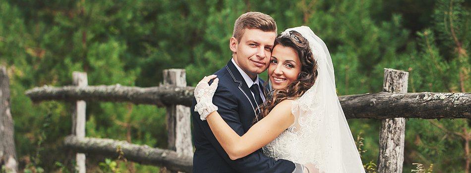 Brautpaar umarmt sich und lächelt in Kamera