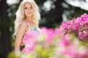 Schöne Frau auf Terrasse mit pinken Blumen