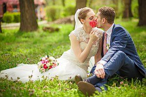 Junges Brautpaar sitzt im Freien, küssen sich, romantisch