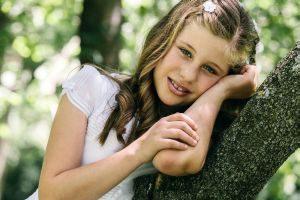 Junges Mädchen lehnt am Baum, Kommunion