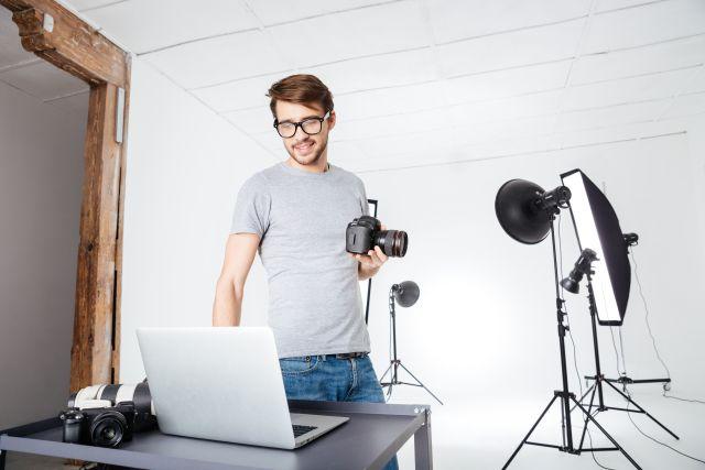 Fotograf im Studio steht vor seinem Laptop