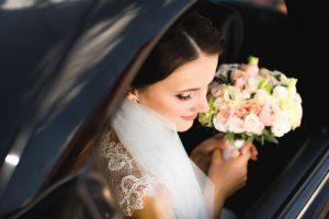 Braut im Auto mit Brautstrauss
