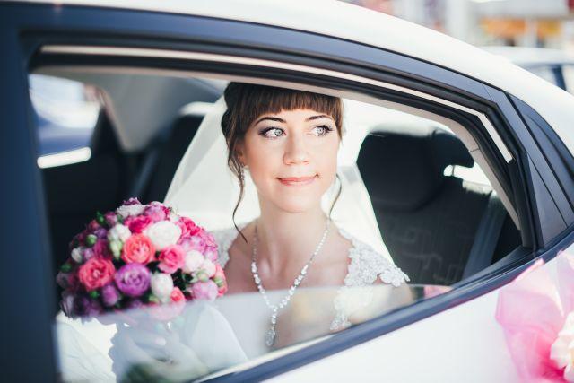 Braut im Auto blickt aus Fenster