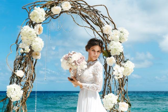 Braut mit Brautstrauss unter Blumenbogen am Strand