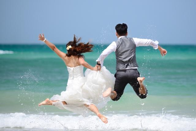 Brautpaar macht Luftsprung am Meer
