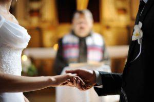Brautpaar hält Hände in der Kirche
