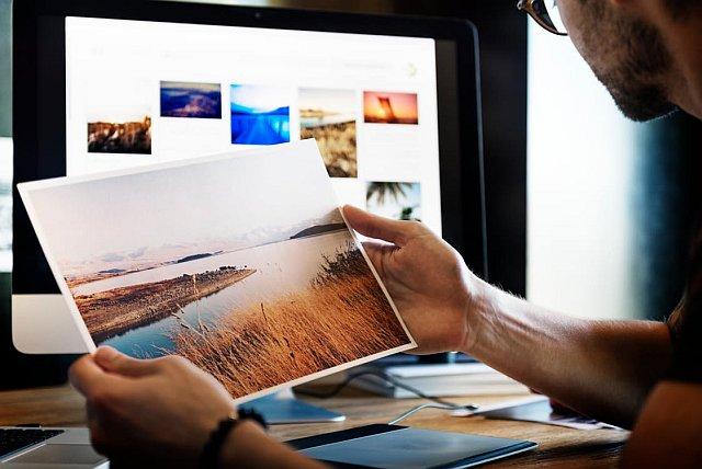 Fotograf betrachtet Bilder am PC