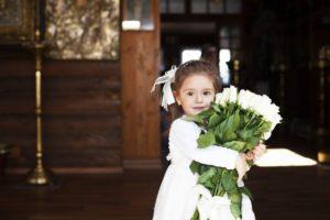 Kleines Mädchen mit Blumen in der Kirche